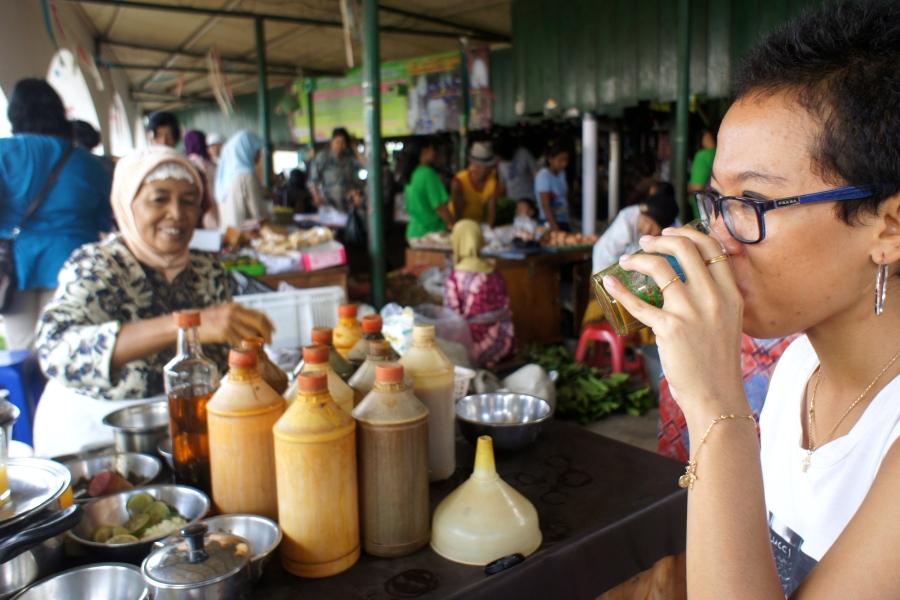 Drinking a glass of fresh homemade 'jamu galian rapat'