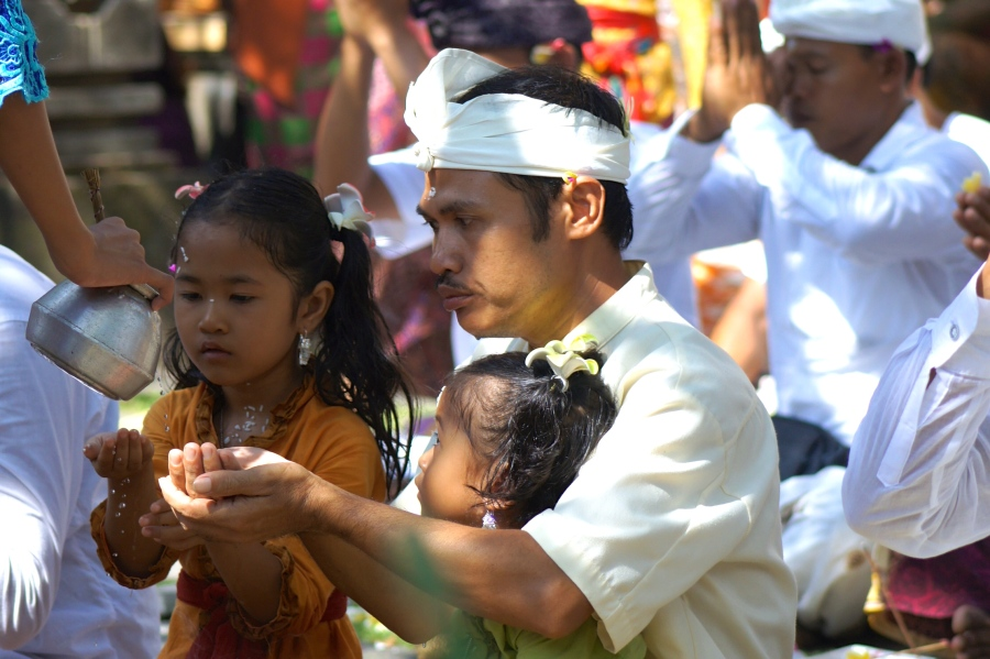 Balinese family were receiving holy water before starting their prayer. [2013: E O]