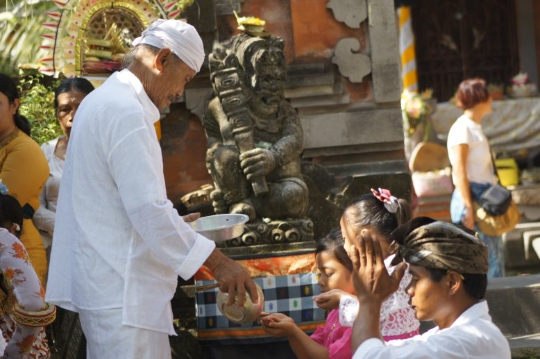 Pemangku / Priest gave holy water to Balinese before they started their morning prayer on Galungan day in the Nyuh Kuning temple [2013: E O]