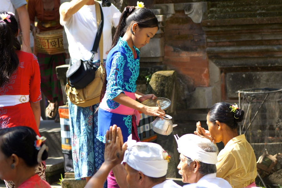 Jero truno truni helped Pemangku to give holy water to the Hindu Balinese before they started their prayer [2013: E O]