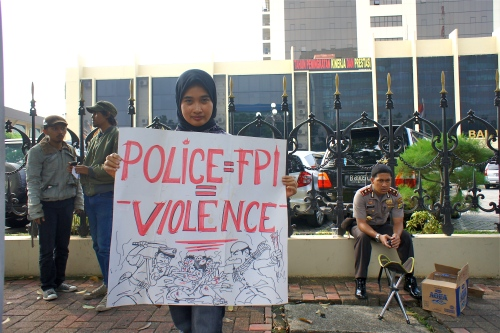 An FPI-Free Indonesia supporter holds a sign at a rally attended by about 50 people in front of the National Police Headquarters in Jakarta on May 10th, 2012. The group is demanding a stop to violence committed in the name of religion. [2012: Oktofani Elisabeth]